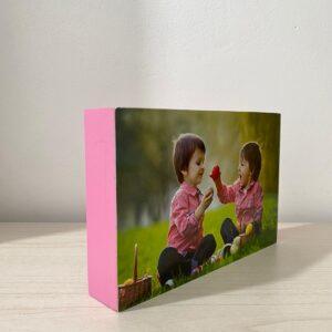 """תמונה על בלוק מעץ בצבע ורוד בגודל 10X15 ס""""מ"""